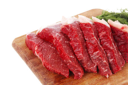 of raw: fresh raw beef meat steak slices on wooden cut board isolated over white background