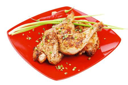piernas: sabrosa comida: pollo asado piernas adornados con brotes verdes y los pimientos en la placa de color rojo aisladas sobre fondo blanco Foto de archivo