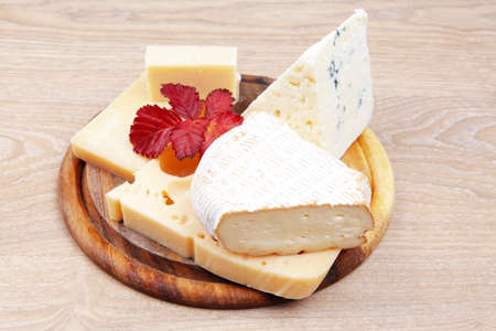 cheese platter: edam parmesan and brie cheese on wooden platter over wooden table