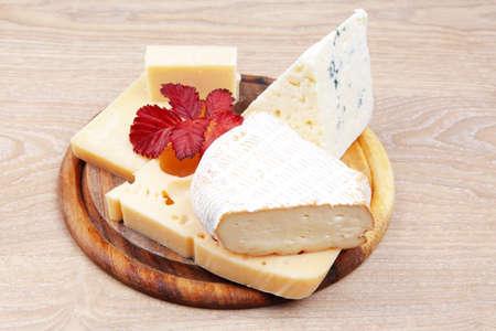 queso blanco: parmesano y queso brie Queso edam en bandeja de madera sobre la mesa de madera