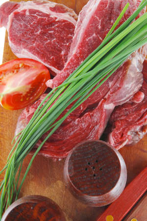 pepper castor: main course : fresh raw beef steak entrecote ready to prepare on cut board with green chives and tomatoes isolated on white background