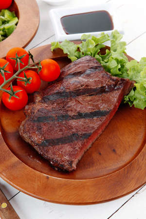 lunch table: lunch of fresh rich juicy grilled beef meat steak fillet with marks on wooden plate over white table served with vegetable salad and cutlery, new york styled cuisine