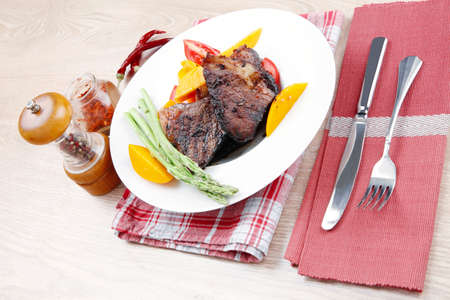 meat food : rare medium roast beef fillet with mango tomatoes and asparagus , served on white dish on red table map over wooden table Stock Photo