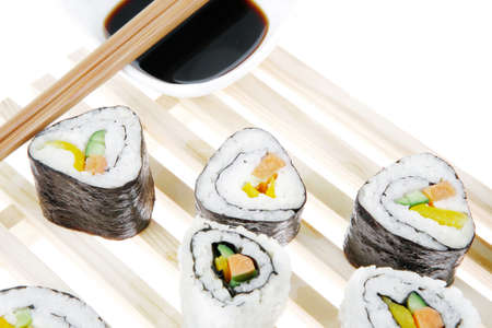 soysauce: California Roll with Avocado and Salmon, Cream Cheese and Raw Salmon inside. on wooden grid . isolated over white background . Maki Sushi and Sashimi