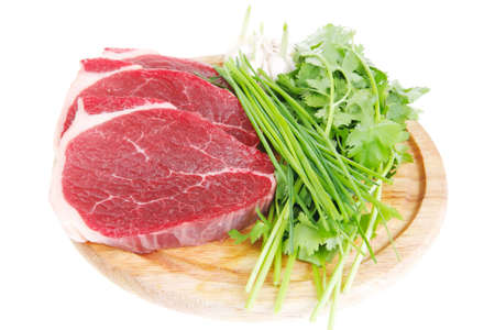 green stuff: uncooked meat : raw fresh beef pork fillet ready to cooking with garlic and green stuff over wood isolated over white background