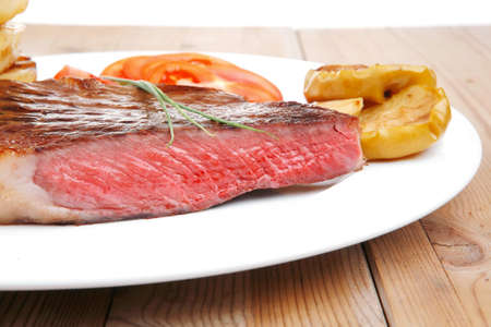 meat food: meat food : roasted fillet mignon on white plate with tomatoes and chives served on wooden table
