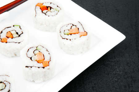 soysauce: Maki Sushi - California Sushi Roll with Avocado, Cream Cheese and Raw Salmon inside With wasabi over black table
