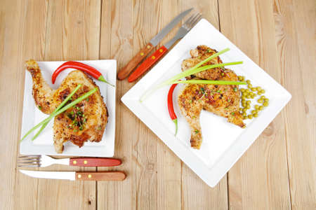 fine legs: meat : chicken quarters garnished with green sweet peas and and cutlery on white plates over wooden table Stock Photo