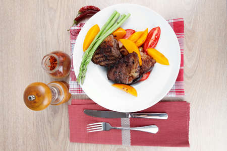 frame less: meat food : grilled beef fillet with mango tomatoes and asparagus , served on white dish on red table map over wooden table