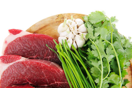 green stuff: butchery : fresh raw beef lamb fillet ready to cooking with green stuff on wooden plate isolated over white background