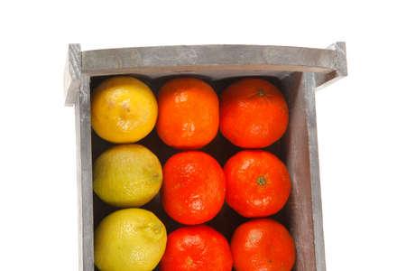 over packed: limone fresco crudo e mandarino confezionato in scatola di legno pronto per il trasporto isolato su sfondo bianco Archivio Fotografico