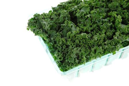 over packed: la col rizada verde fresca cruda envasado en caja de pl�stico listo para vender aislado m�s de fondo blanco