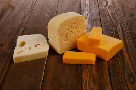 swiss cheese: various types of fresh raw aged delicatessen cheese on wooden table cheddar edam swiss