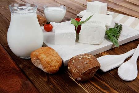 latte fresco: bianco fresco greco formaggio feta con latte in asparagi vaso di basilico ciliegia pomodoro e panino francese su tagliere su tavolo di legno scuro