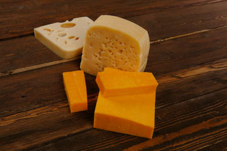 edam: various types of fresh raw aged delicatessen cheese on wooden table cheddar edam swiss