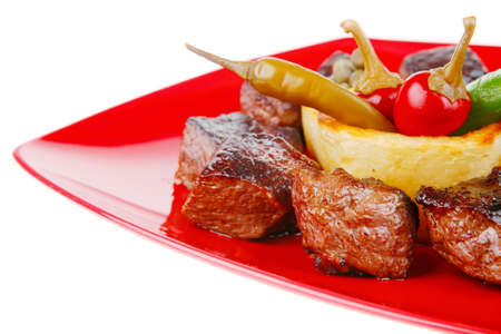 european food: european food: grilled beef meat on red china plate isolated on white background with capers and bbq sauce