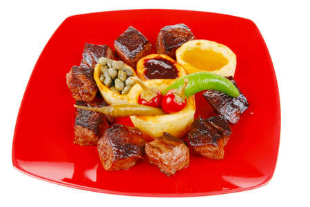 european food: european food: grilled beef meat on red china plate isolated on white background with capers and bbq sauce . shallow dof
