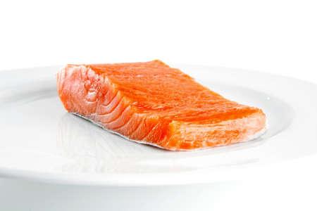 a portion: smoked fresh salmon piece on a big white dish Stock Photo