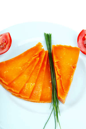sustained: old delicious cheddar cheese chop with slice on blue plate with tomatoes and chives isolated over white background Stock Photo