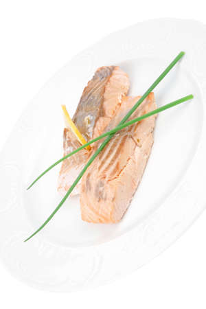 entree: savory sea fish entree : roasted salmon fillet with green onion, and lemon on white plate isolated over white background