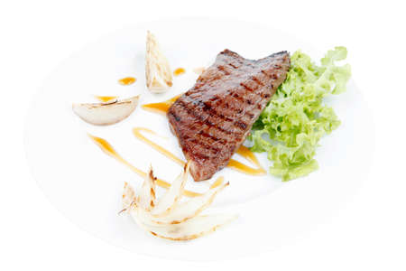 frame less: meat food : grilled steak on green lettuce salad , with roast onion, on dish isolated over white background