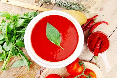 aceite de cocina: alimento de la dieta: sopa fresca de tomate fr?a con albahaca y el tomillo pimiento seco en un recipiente grande en la mesa de madera