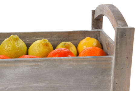 over packed: fresh raw lemon and mandarin packed in wooden box ready for transportation isolated over white background
