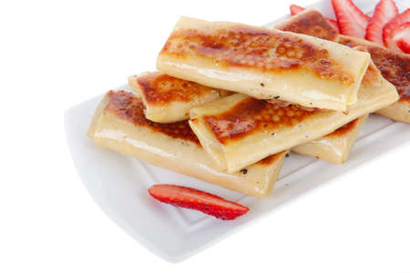 russian food: russian food - heap of sweet pancake filled with cottage cheese with strawberry served on white plate isolated over white Stock Photo