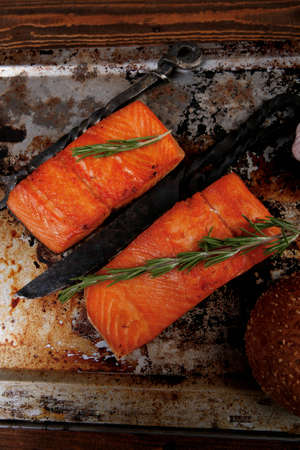 fresh salmon: delicious portion of raw fresh salmon fillet with aromatic herbs and spices on vintage tray over wooden table - healthy food, diet cooking concept