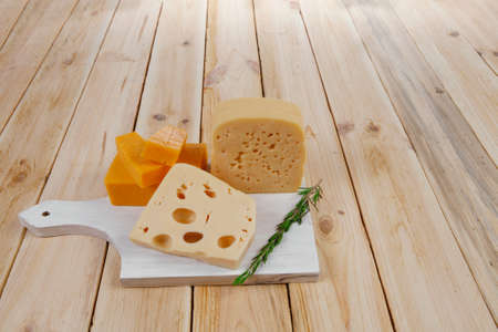edam: various types of fresh raw aged delicatessen cheese on white plate over light wooden table cheddar edam swiss Stock Photo