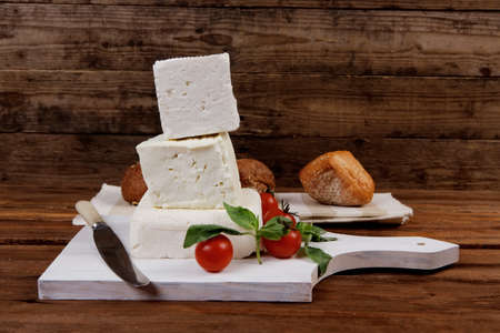 white cheese: dairy healthy food fresh white greek goat sheep feta cheese on wood cutting plate with cherry tomatoes and french bun over dark wooden table