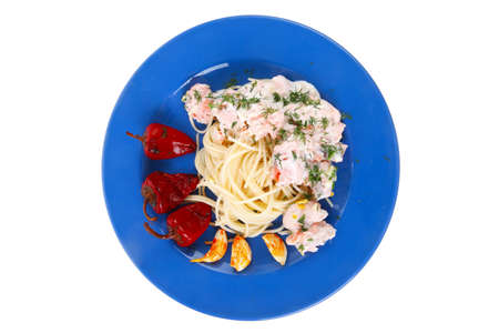 fruit plate: fresh rose wild salmon baked in cream cheese sauce with italian pasta and red hot pepper on blue plate isolated over white background Stock Photo