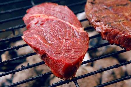 barbequing: fresh raw beef fillet steak red meat on big round barbecue brazier black grid full burned charcoal