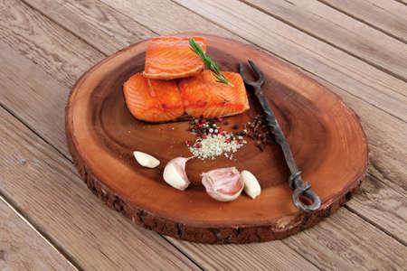 ajo: desayuno delicioso porción de fresco filete de salmón asado con especias secas ajo y romero en la placa de madera con negro forjado tenedor hecho a mano