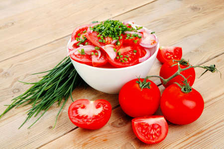 tomate ensalada: healthy food : fresh tomato salad in white bowl with bunch of chives and raw tomatoes on twig , onion,  over wooden table