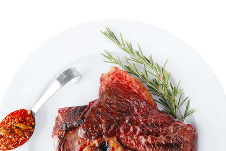 meat food: meat food : grilled beef steak served on white plate with red thin chili pepper and spices isolated over white background
