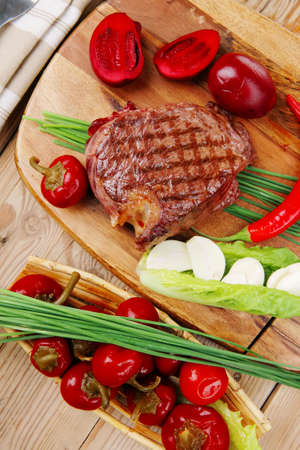 meat food: meat food : roast beef garnished with green staff and red chili hot pepper on wooden table with cutlery