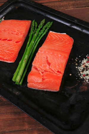 two piece: two piece of fresh raw pink salmon on black tray with rosemary and asparagus dry spices healthy food diet cooking concept