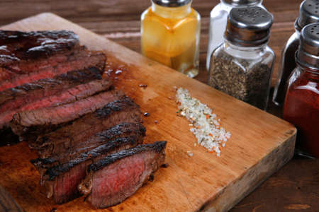 pepperbox: fresh roast red beef meat fillet mignon cutted on wooden plate with vintage fork many different kinds of dry spice over table