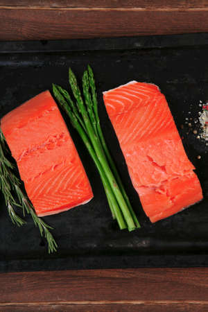 rosmarin: two piece of fresh raw pink salmon on black tray with rosemary and asparagus dry spices healthy food diet cooking concept