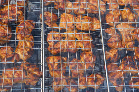 serv: fresh raw chickn in meat holder on grid grill over burned charcoal spiced with salt pepper paprika ready to serv party