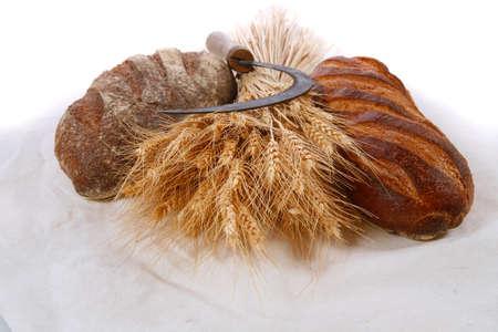 Haufen gemähten Weizenähren mit Vintage handmade reaper Haken Sichel und Roggen und weiß dunkel französisch frisch Laib Brot auf hellem Leinentischdecke