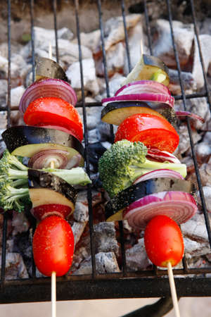 barbequing: shish kebab fresh raw vegetables tomato red onion cherry broccoli eggplant on skewer over grid charcoal brazier ready to cook