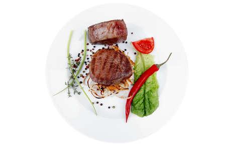 carne asada: Solomillo de buey a la parrilla con tomate en placa aislada sobre fondo blanco, pimiento rojo caliente y tomillo Foto de archivo