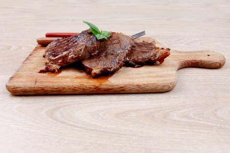 carne asada: carne a la parrilla en plato de madera con cubiertos sobre la mesa