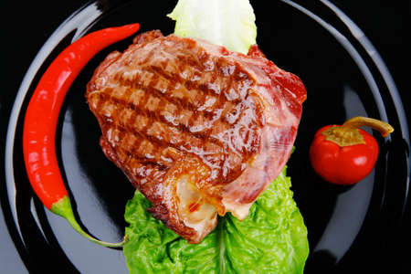 mouthful: meat food : roast beef garnished with green lettuce and red chili hot pepper on black dish isolated over white background