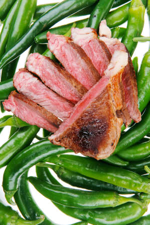 meaty: meaty food : grilled red meat steak sliced on a green hot chili peppers on a white back background