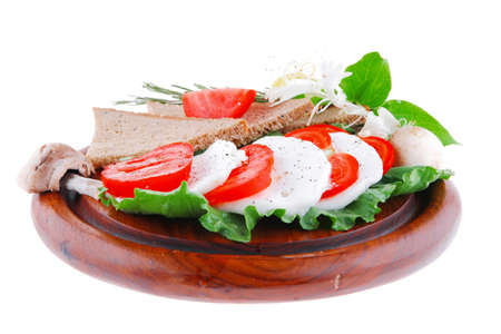 tomato slices: mozzarella and tomato slices on wooden plate Stock Photo