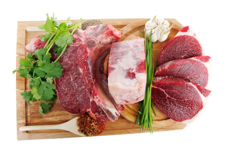 green stuff: uncooked meat : raw fresh beef pork rib and fillet ready to cooking with garlic and green stuff over wood isolated on white background
