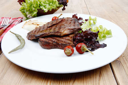 frame less: meat food : roast steak boneless with roast onion and red hot peppers, served on green lettuce salad on dish isolated over wooden table